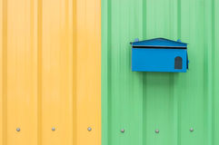 Blue mail box on orange and green corrugated metal sheet as back Stock Photography