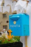 Blue mailbox with the emblem of the USSR and yellow wooden anchor. Old blue mailbox with the emblem of the USSR and yellow wooden anchor Stock Photos