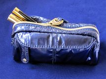 Blue Makeup Bag. Mindnight blue makeup bag with mascara, concealer and eyeliner on a matching blue background Royalty Free Stock Photography