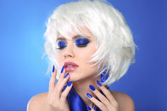 Blue makeup. Blonde bob hairstyle. Blond hair. Fashion Beauty Gi. Rl portrait. Sexy lips. Manicured nails and Make-up. Vogue Style Woman  on blue background Stock Images