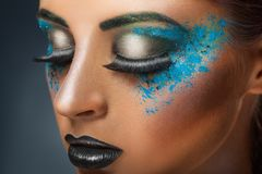 Blue makeup. Close-up of a young woman with blue makeup on a dark background Royalty Free Stock Photos