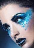 Blue makeup. Close-up of a young woman with blue makeup on a dark blue background Stock Images