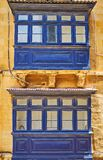 The blue Maltese balconies, Valletta, Malta. The close-up of two dark blue wooden Maltese balconies, decorated with geometrical pattern and stone garlands Royalty Free Stock Photos
