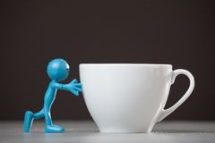 Blue man pushing and coffee cup. Blue man pushing a coffee cup. Concept Stock Image