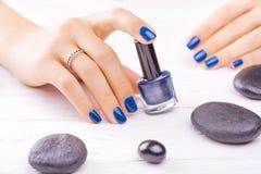 Blue manicure with black stones. Beautiful blue manicure with black stones on the white royalty free stock image