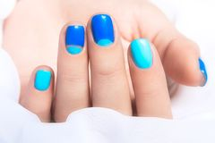 Blue manicure in light and dark colors of lacquer. On a white background. Nail art design stock photography
