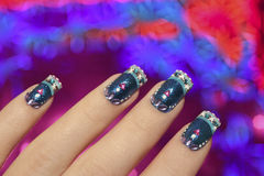 Blue manicure with snowflakes. Beautiful winter blue manicure with snowflakes on a brilliant background in the form of snowflakes stock photo