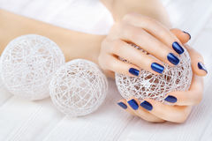 Blue manicure with a white ball of yarn Stock Photo