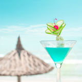 Blue margarita cocktail with lime fruit and cherry decoration. At tropical ocean beach with umbrella.. Vintage style, hipster colors image with copy space for Stock Image