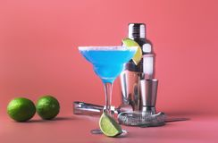 Blue margarita exotic alcoholic cocktail with tequila, liqueur, lime juice, salt and ice, summer blue background, place for text stock photos