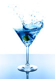 Blue martini. With olive in glass. Splash with drops over white background Royalty Free Stock Photos