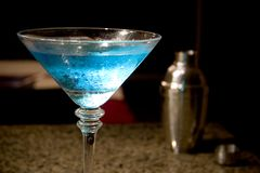Blue Martini and shaker. Blue raspberry martini with the martini shaker in the background royalty free stock photography