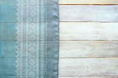 Blue material with ornament and grunge wood board background. Surface of aged white wooden planks and painted shawl fabric, top view, empty place Royalty Free Stock Image
