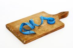 Blue Measuring Tape on Brown Wooden Chopping Board Stock Photo