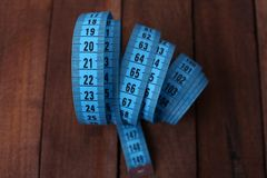 Blue measuring tape on wooden background Royalty Free Stock Image