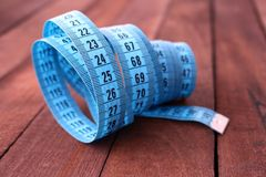Blue measuring tape on wooden background Stock Image