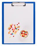 Blue medical clipboard with pills and tablets Royalty Free Stock Photography