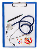 Blue medical clipboard with stethoscope and pills Stock Photo