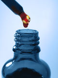 Blue medicine bottle. Red drops in blue bottle Royalty Free Stock Photos