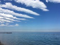 Blue Mediterranean sea, smoothly passing into the sky with beautiful clouds. Located strips, above the water, far pier, the beach of the Turkish resort Royalty Free Stock Photos