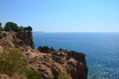 Blue Mediterranean Sea with a steep coast on a sunny day. City o stock photos