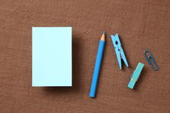 Blue memo note pad and colored pencil, clips on fabric background. Blue memo note pad and colored pencil, clips on brown fabric background stock photos