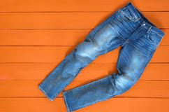 Blue mens jeans denim pants on orange background. Contrast satur. Ated color. Fashion clothing concept. View from above Stock Photo