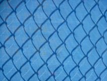 Blue mesh fencing with shadows Royalty Free Stock Photography