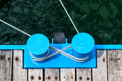 Blue metal bollard marina with rope Stock Photos