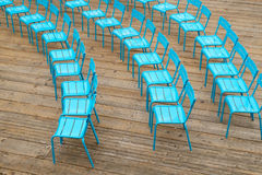 Blue metal chairs on wood deck. Seattle, WA, USA July 7, 2016: Three curved rows of blue metal chairs on wooden deck along Seattle, Washington waterfront before Royalty Free Stock Photography