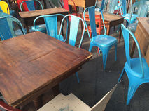 Blue metal chairs and wooden tables Royalty Free Stock Images