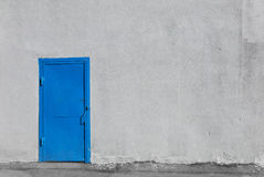 Blue metal door on gray stucco building wall Royalty Free Stock Image