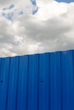 Blue Metal Fence and Large White Clouds Royalty Free Stock Photography