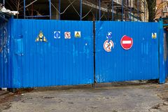 Entrance to the construction site. Blue metal fence with warning signs on the building site royalty free stock images