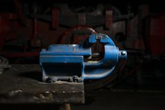 Blue metal mechanical vise mounted on a workbench in the repair shop.  stock photo