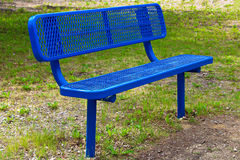 A blue metal mesh bench on the grass.  royalty free stock image