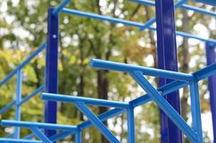 Blue metal pipes and cross-bars against a street sports field for training in athletics. Outdoor athletic gym equipment. Macro ph. Oto with selective focus and Royalty Free Stock Photo
