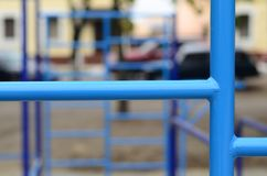 Blue metal pipes and cross-bars against a street sports field for training in athletics. Outdoor athletic gym equipment. Macro ph. Oto with selective focus and Stock Photos