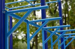 Blue metal pipes and cross-bars against a street sports field for training in athletics. Outdoor athletic gym equipment. Macro ph. Oto with selective focus and Royalty Free Stock Photos