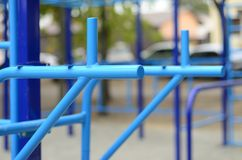 Blue metal pipes and cross-bars against a street sports field for training in athletics. Outdoor athletic gym equipment. Macro ph. Oto with selective focus and Royalty Free Stock Images