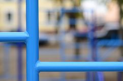 Blue metal pipes and cross-bars against a street sports field for training in athletics. Outdoor athletic gym equipment. Macro ph. Oto with selective focus and Stock Photo