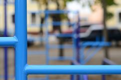 Blue metal pipes and cross-bars against a street sports field for training in athletics. Outdoor athletic gym equipment. Macro ph. Oto with selective focus and Stock Images