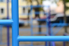 Blue metal pipes and cross-bars against a street sports field for training in athletics. Outdoor athletic gym equipment. Macro ph. Oto with selective focus and Stock Image