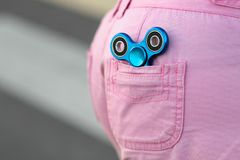Blue metal popular fidget spinner in the back pocket of pink jeans shorts, anxiety relief toy, anti stress and relaxation fidgets.  stock photography