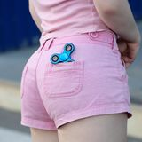 Blue metal popular fidget spinner in the back pocket of pink jeans shorts, anxiety relief toy, anti stress and relaxation fidgets.  stock photo