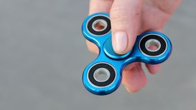Blue metal popular fidget spinner toy on the palm of your hand, take it.  royalty free stock image