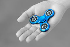 Blue metal popular fidget spinner toy on the palm of your hand, take it, black and white, monochrome photo Royalty Free Stock Image