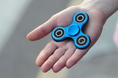 Blue metal popular fidget spinner toy on the palm of your hand, take it.  stock image