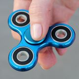 Blue metal popular fidget spinner toy on the palm of your hand, take it.  royalty free stock photography