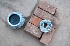 A blue metal round pot, orange and brown rectangular bricks laying together and a white rag wrapped in a circle, on a gray backgro Stock Photography